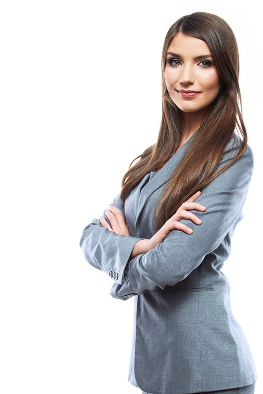 Millennial woman with long brown hair with arms crossed wearing a grey suit