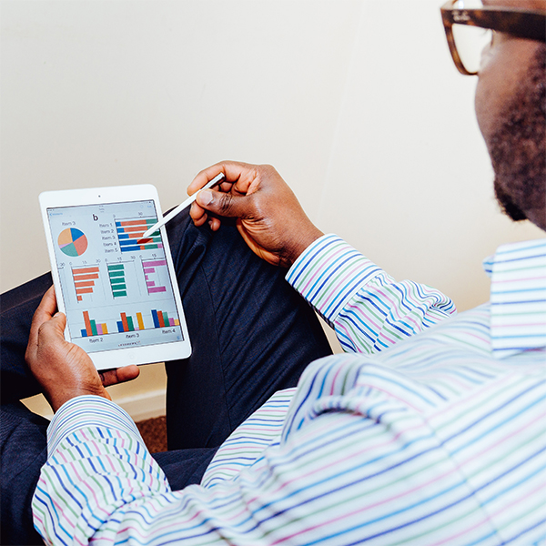 Side view of a business man holding a tablet and clicking on the screen showing charts with a stylus