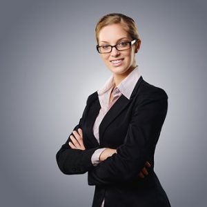 Millennial business woman with black square glasses and a black blazer with her arms folded across her chest