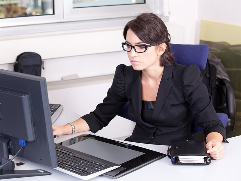 Millennial woman with brown hair and glasses wearing a black blouse looking at her desktop computer monitor
